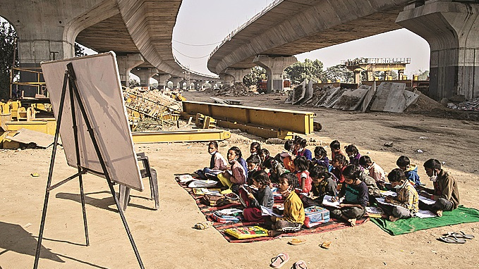 Underprivileged children study while seated on mats on the ground at an improvised classroom set up at a construction site on December 09, 2020 in New Delhi, India. Many underprivileged children are unable to afford the laptops or tablet computers needed for online classes, leaving them without access to education as the Covid-19 pandemic rages across India. The improvised school, set up by graduate students who are still looking for work, is located at a construction site underneath a metro railway track in the dusty streets of the country's capital. The pandemic is hit the underprivileged members of society the hardest, forcing millions of people out of work, out of homes, and back into destitution, as the country quickly approaches a tally of 10 million infections.
