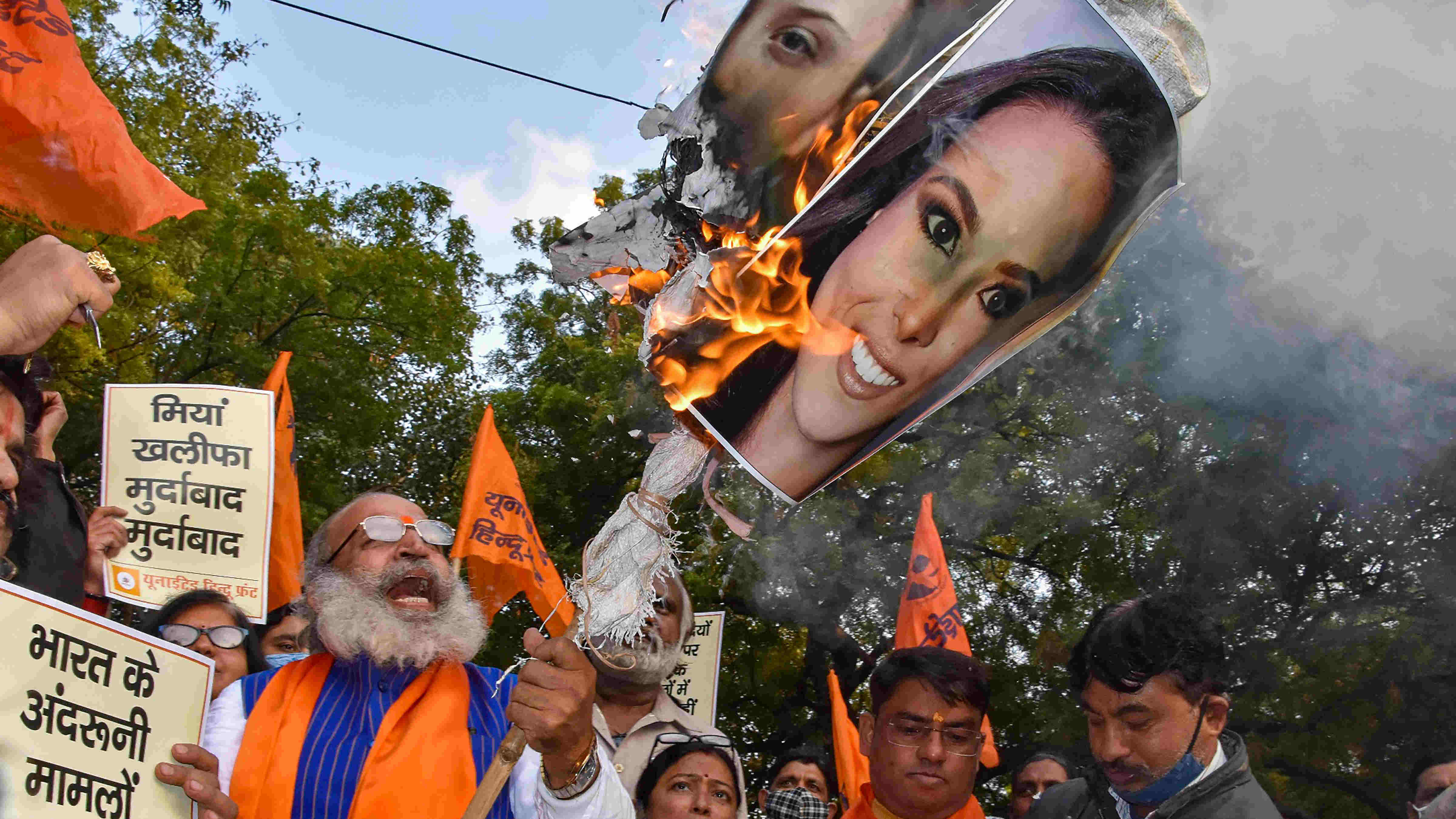 United Hindu Front supporters burn posters of international activists and celebrities, who supported the ongoing farmers protest against the new farm laws, at Jantar Mantar in New Delhi, Thursday, Feb. 4, 2021.
