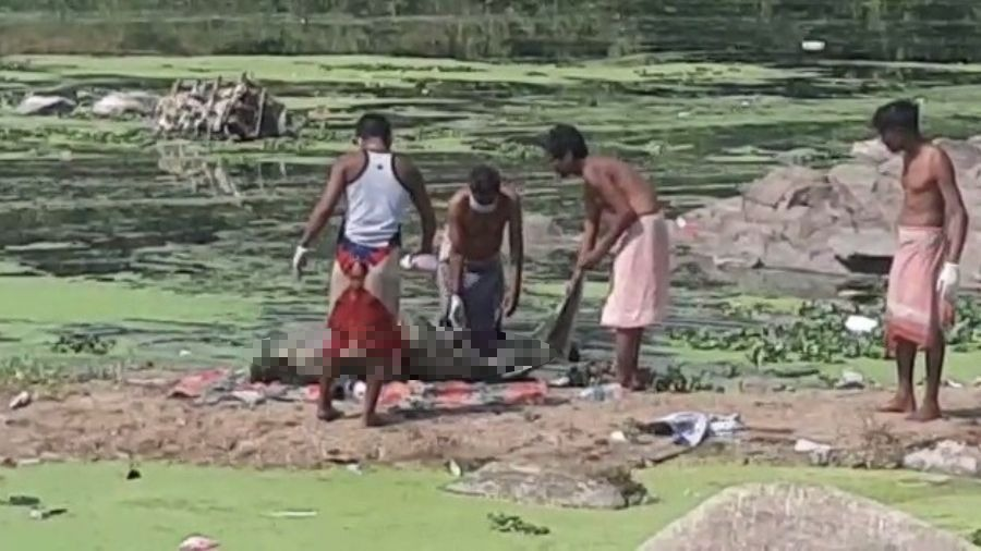 Men fish out the body of missing Sanjay Chutel from the Subernarekha river on Tuesday.