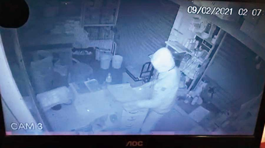A grab of the CCTV footage shows a burglar in PPE