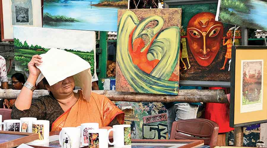 A woman shields herself from the sun while managing a stall at an exhibition in front of the  Academy of Fine Arts on Sunday.