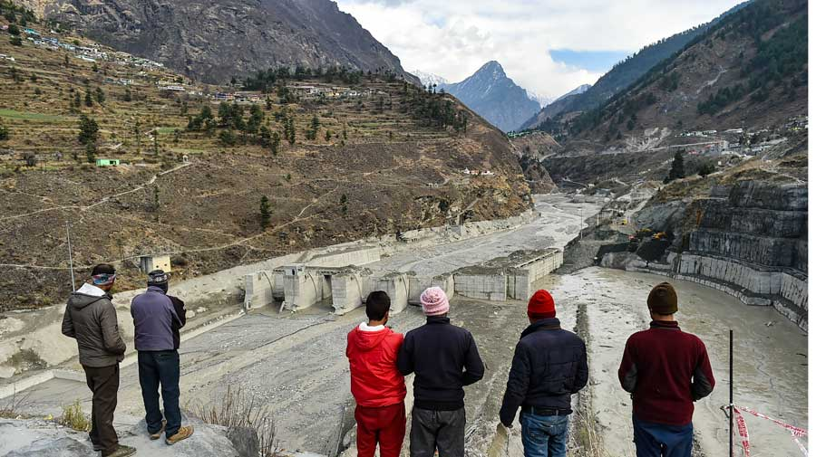 People watch the rescue and restoration work at damaged Tapovan barrage in Chamoli district of Uttarakhand on Wednesday.