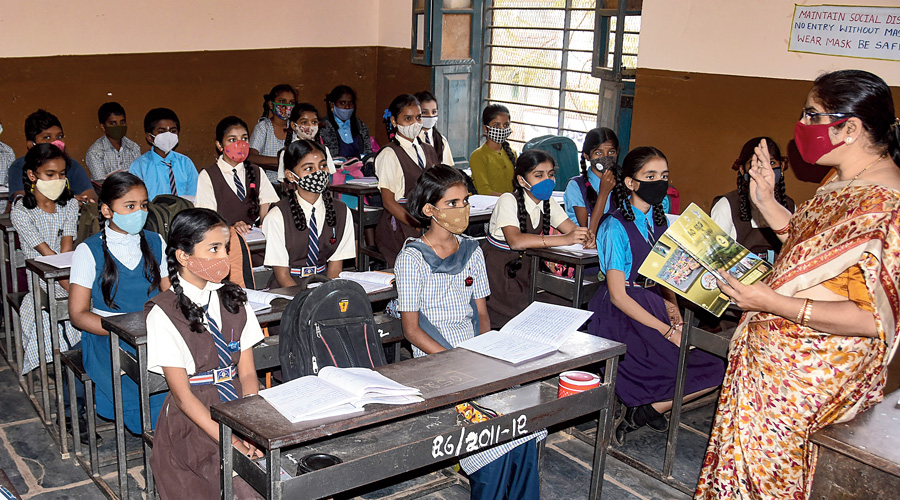 Students in Hubballi, Karnataka, attend a class after their school reopened  on Monday.