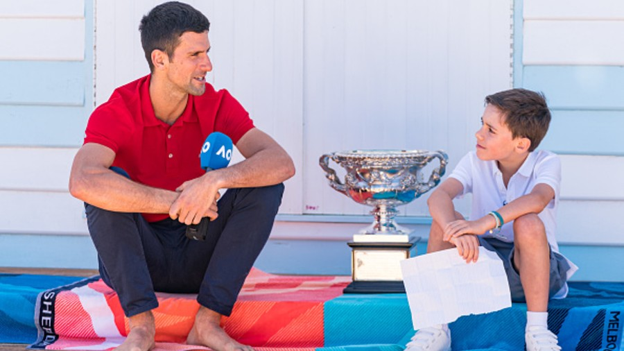 Novak Djokovic shows his Australian Open men's trophy to a young fan at Melbourne's Brighton Beach on Monday
