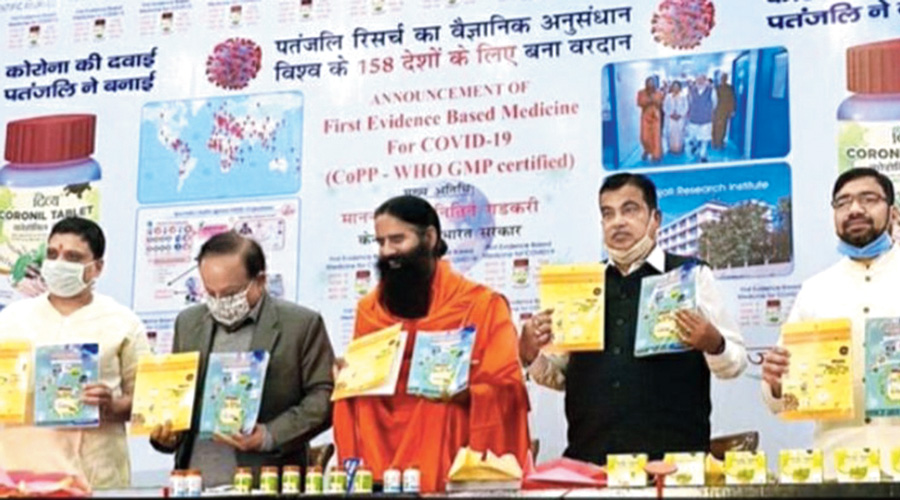 """Behind Harsh Vardhan (left), Ramdev (centre) and Nitin Gadkari is the banner with the word """"WHO"""" at the event in New Delhi on Friday."""