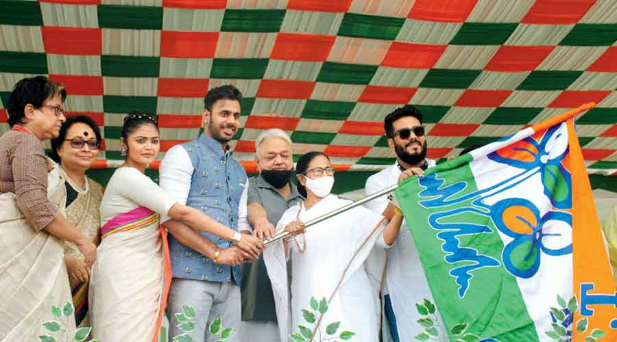 Cricketer Manoj Tiwari and film personalities receive a Trinamul flag from Mamata at Sahaganj on Wednesday
