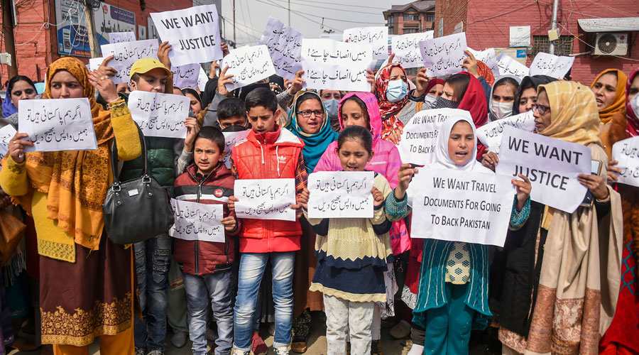 Pakistan-origin family members of former Kashmiri militants raise slogans and hold placards during a protest march, demanding travel documents for enabling them to visit their family in Pakistan, in Srinagar on Tuesday, Feb. 23, 2021.