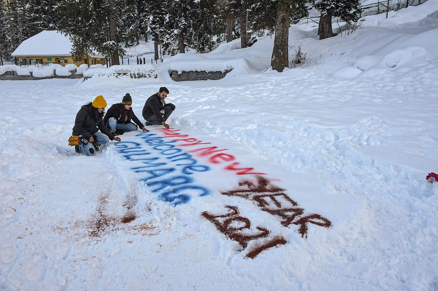 Tourists sit near Happy New Year 2021 sign on snow at the famous ski resort of Gulmarg in north Kashmir on the eve of the New Year on Thursday.