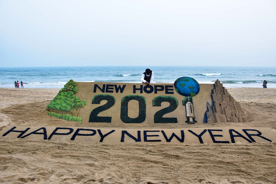 Sand artist Sudarshan Pattanaik creates a sand sculpture to welcome the year 2021, at Puri beach on Thursday.