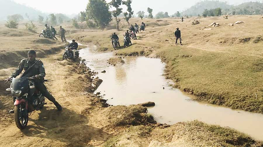 CRPF and  police teams cross a stream and rough terrain to reach the village.