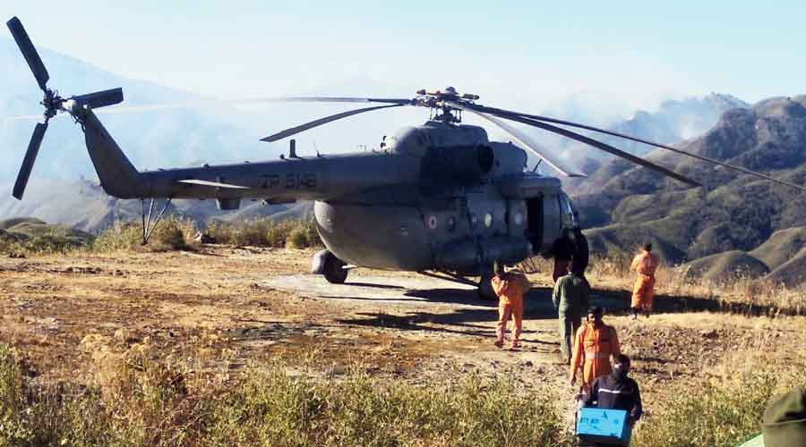 NDRF personnel carry food and equipment to the base camp from an IAF chopper