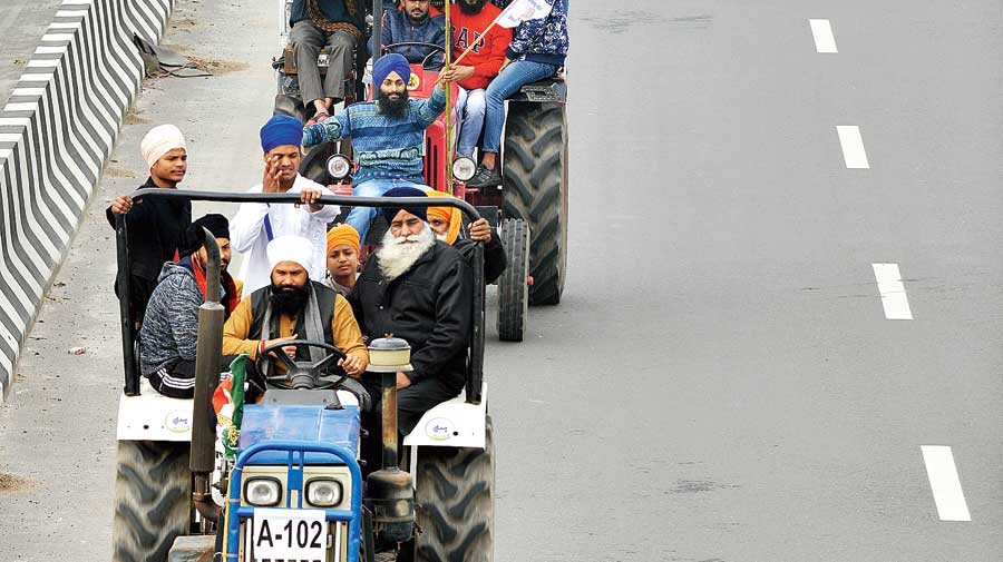 Farmers protesting against the new farm laws take part in a tractor rally at the Ghazipur border near Delhi on Thursday.