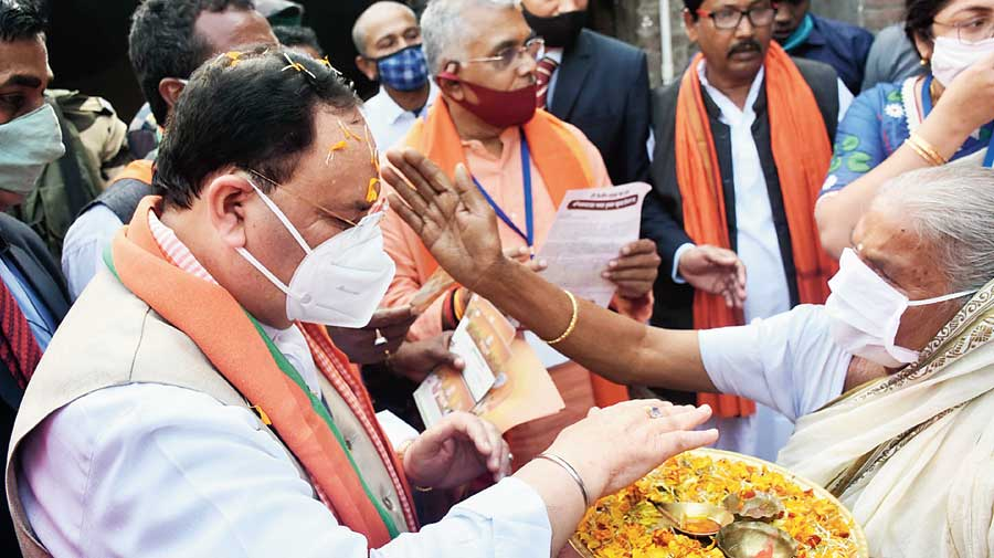 JP Nadda accepts blessings from an elderly woman while on his mission to collect a fistful of rice in Katwa.