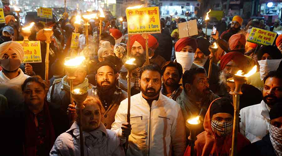 People take part in a torch march in support of farmers protest against the new farm laws, in Jalandhar on Saturday, Jan. 9, 2021.