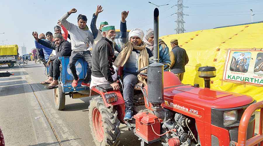 Farmers ride a tractor during their ongoing agitation at Delhi's Ghazipur border on Monday
