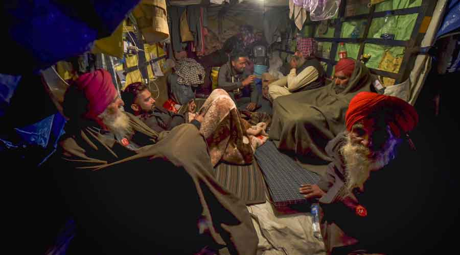 Farmers rest inside a tractor trolley during their agitation against new farm laws