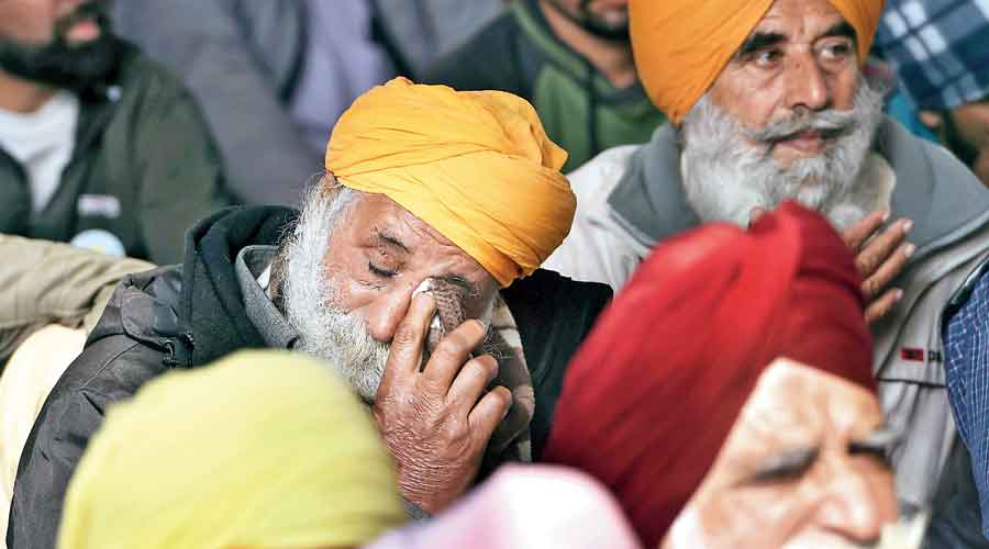 A protester wipes a tear at Singhu border on Wednesday