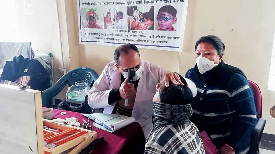 A doctor checks a patient at a Chokher Alo camp