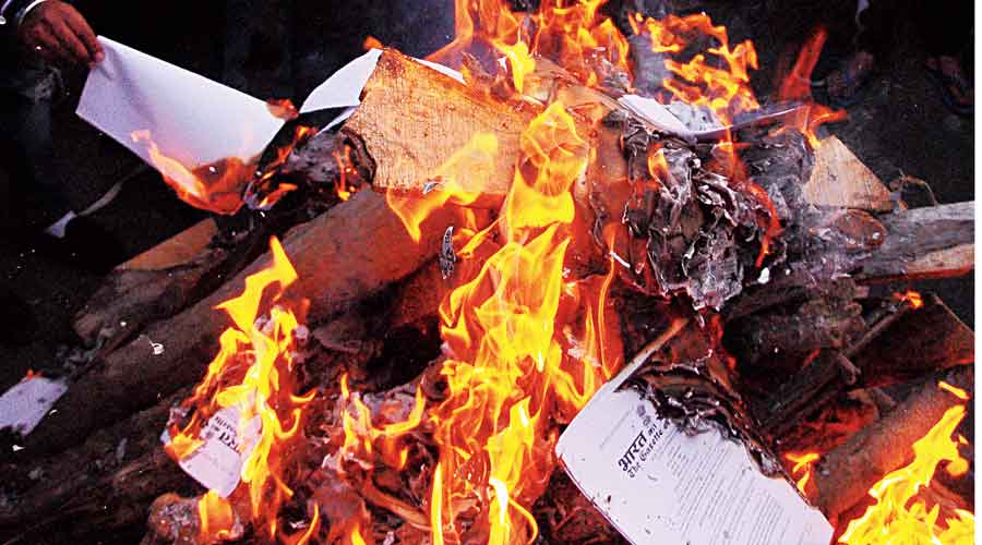 Protesting farmers burn copies of the three farm laws  while celebrating Lohri at the Ghazipur border on Wednesday