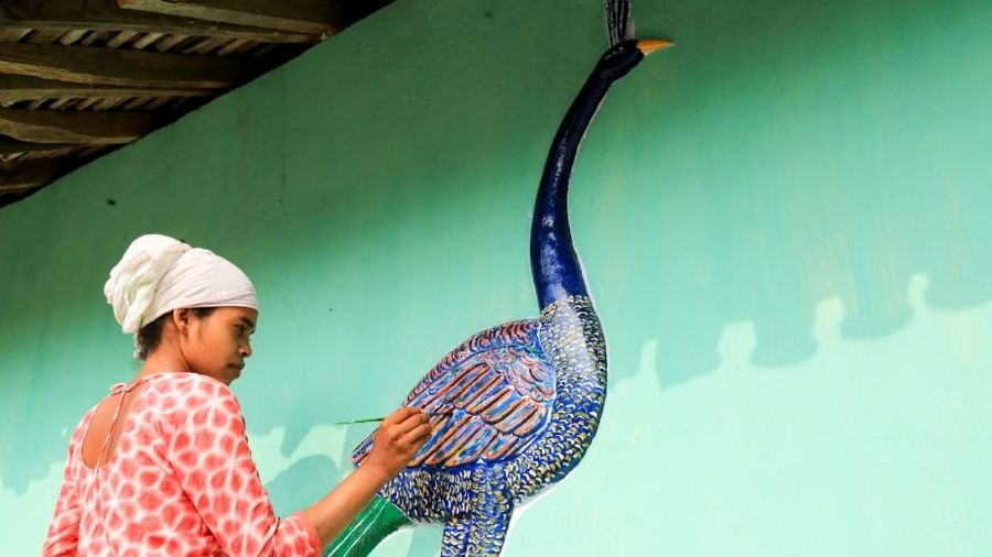 A tribal woman decorates her hut on Wednesday, a day ahead of Makar Sankranti, as part of her community's traditions, at Potka area near Jamshedpur, in East Singhbhum district