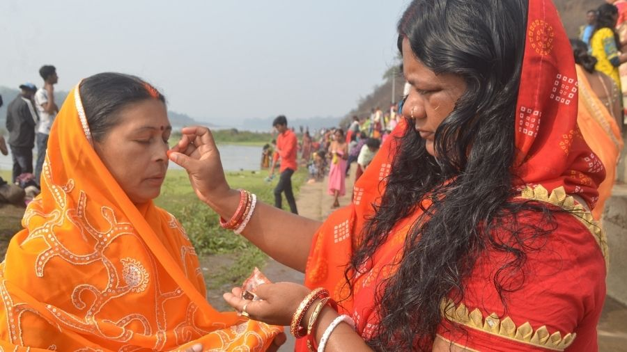A woman applies 'sindoor' on the forehead of another woman, as part of a holy ritual, on the bank of river Damodar at Mohalbani Ghat in Dhanbad on Thursday.