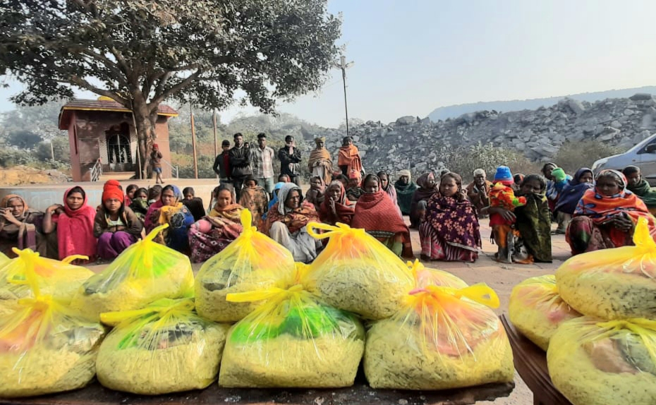 People from the economically weaker sections of the society sit with the food grans that were offered to them on the occasion of Makar Sankranti, at Katras, Dhanbad, on Thursday.