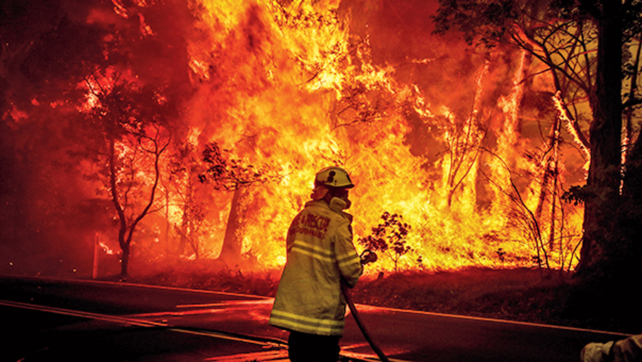 Fire and Rescue personnel prepare to use a hose in an effort to extinguish a bushfire as it burns near homes in the outskirts of Bilpin in Sydney, Australia.