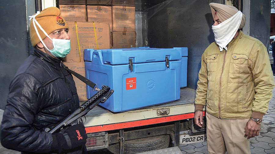 A policeman guards a van containing Covishield vaccine vials in Amritsar  on Thursday.