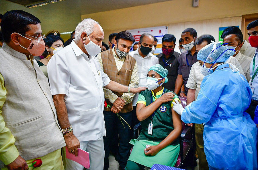 A medic administers the first dose of Covishield vaccine to a health worker in the presence of Karnataka CM BS Yediyurappa, in Bengaluru.