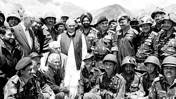 Atal Bihari Vajpayee along with then defence minister George Fernandes, crouching, third from left, then Jammu and Kashmir governor Girish Chandra 'Gary' Saxena, standing second from left, and then army chief General Ved Prakash Malik, fourth from right, meet the troops in Kargil.
