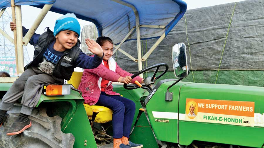 Children play on a tractor at the protest site at Delhi's Ghazipur border on Sunday.