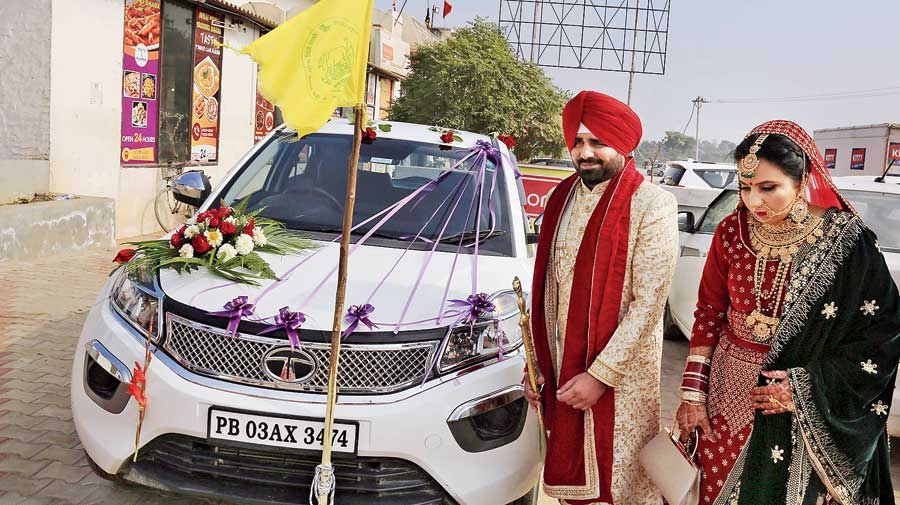 Newlyweds in Bathinda fix a flag on their car on Sunday in support of the farmers' agitation.