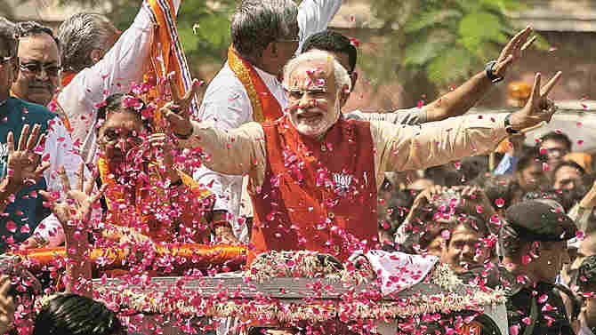 Right:  Supporters throw flower petals as Bharatiya Janata Party (BJP) leader Narendra Modi rides in an open jeep on his way to file nomination papers on April 9, 2014 in Vadodara, India.