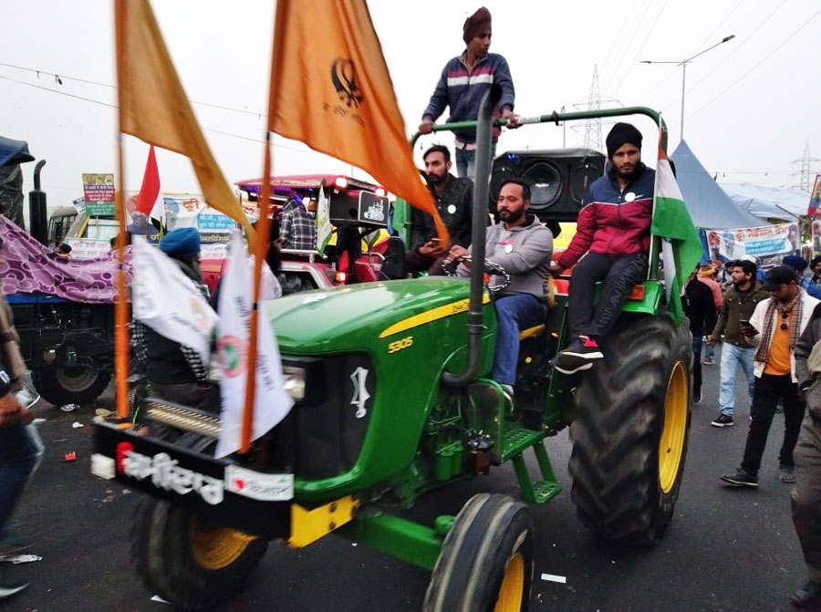 A tractor makes its way through the protest site at Ghazipur.