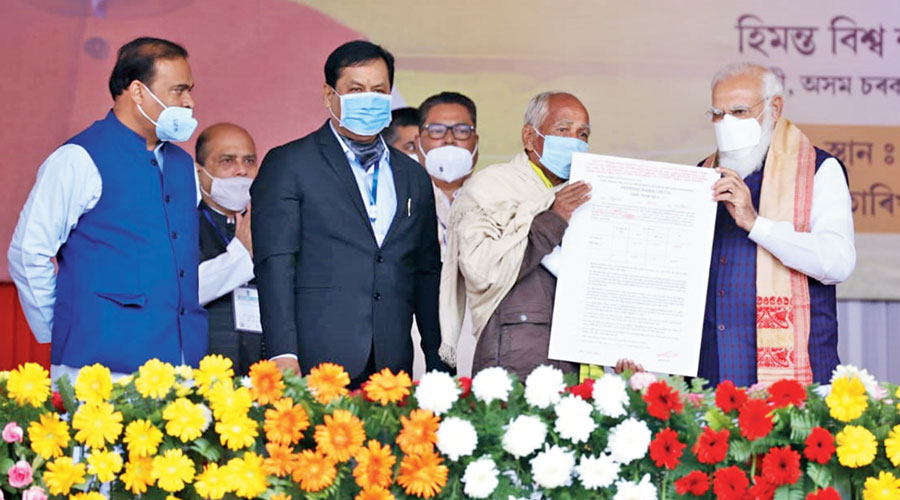 Prime Minister Narendra Modi hands over a land allotment certificate to a beneficiary at Jerenga Pathar in Sivasagar, Assam, on Saturday. Chief minister Sarbananda Sonowal (second from left) and minister Himanta Biswa Sarma (extreme left) are on the dais
