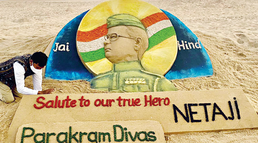 Artist Sudarshan Patnaik creates a sand sculpture at the Puri beach in Odisha on Saturday to pay tribute to Netaji Subhas Chandra Bose on his 125th birth anniversary.
