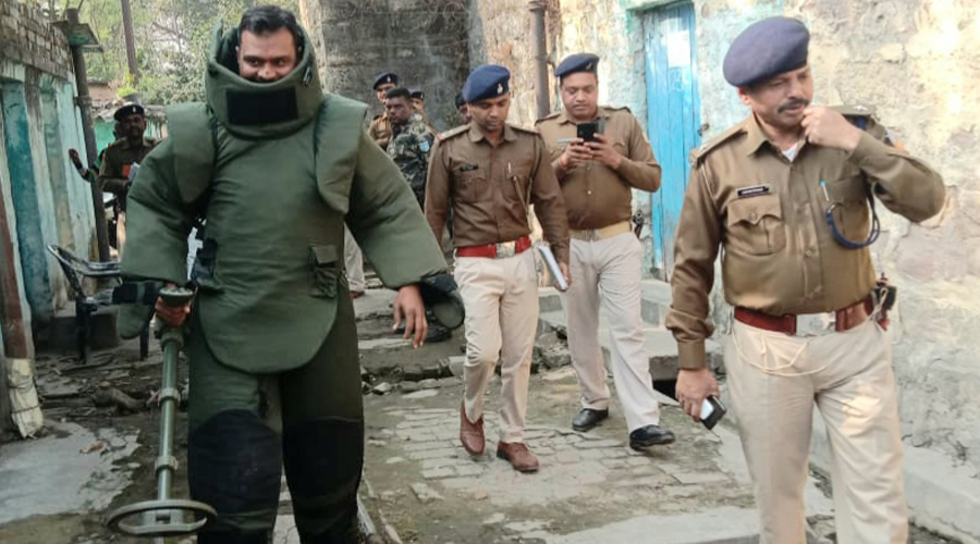 Bomb squad team member and police after disposing three live bombs at the old railway station area under Dhansar Police Station in Dhanbad on Sunday.