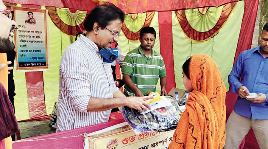 Rammohan Mission High School principal Sujoy Biswas hands over relief materials to a resident of Budhokhali village in the Sunderbans on Saturday