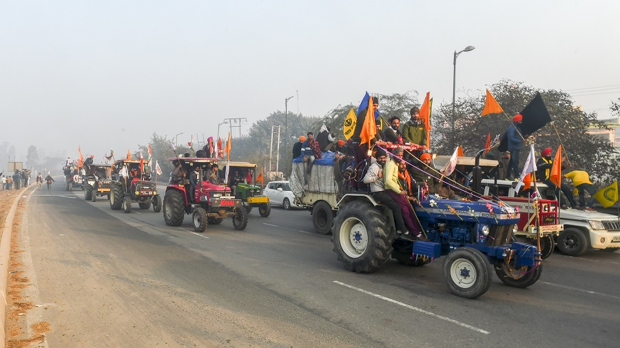 Farmers on their tractors move towards Delhi after breaking the police barricades at Singhu border during their rally on Republic Day, in New Delhi on Tuesday.