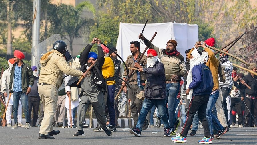 Protesting farmers clash with Delhi Police during their tractor rally in New Delhi, on Tuesday.