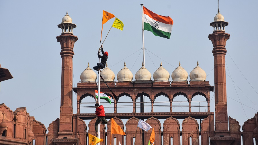 Farmers hoist flags at the Red Fort during the Kisan Gantantra Parade amid the 72nd Republic Day celebrations, in New Delhi on Tuesday.