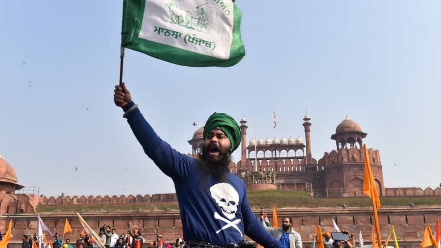 A farmer waves a flag along with others in front of the Red Fort in New Delhi, on Tuesday.