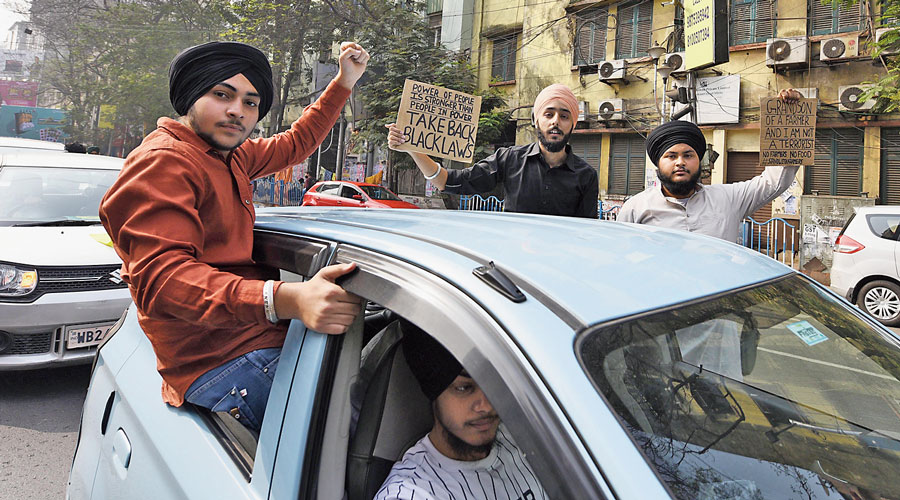 Participants in the car rally hold posters against the Centre's farm laws on Central Avenue on Tuesday.