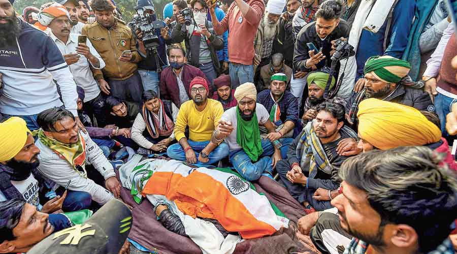 Farmers near the body of a protestor who died after his tractor overturned during the  tractor rally in New Delhi on Republic Day