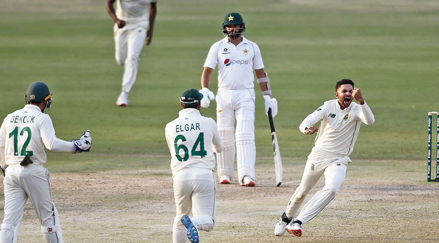 Keshav Maharaj of South Africa (right) celebrates with teammates after dismissing Pakistan's Babar Azam on the first day of the first Test in Karachi on Tuesday.
