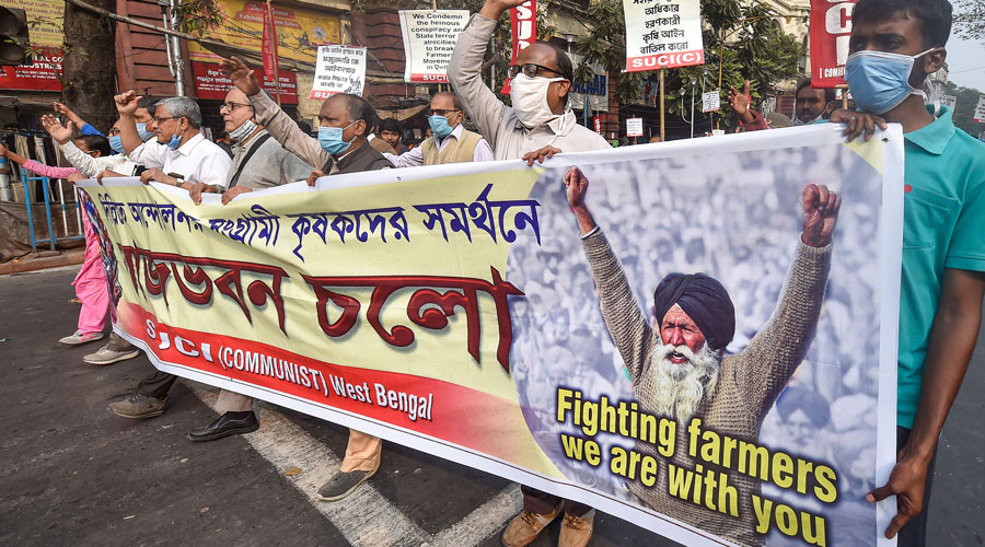 SUCI activists raise slogans against the Centre during their march to Governor House, to protest against new farm law, in Kolkata, on Tuesday.