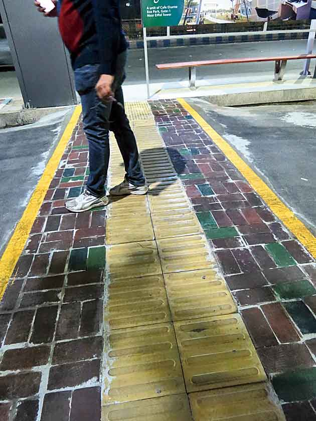 A barrier-free ramp made of plastic paver and tactile tiles.