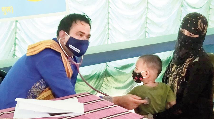 Kafeel Khan examines a child at a camp in Kankinara on Thursday.