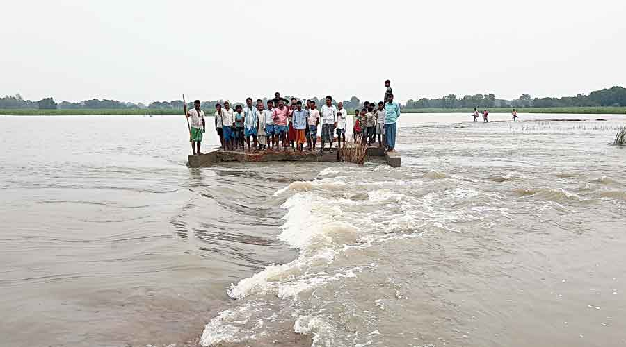 Villagers take refuge on a road surrounded by swirling floodwater in West Champaran