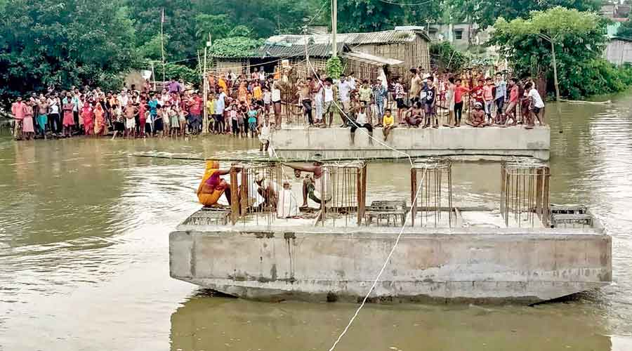 Villagers gather near an under-construction bridge in a flood-affected area in Madhubani, Bihar, on Wednesday.